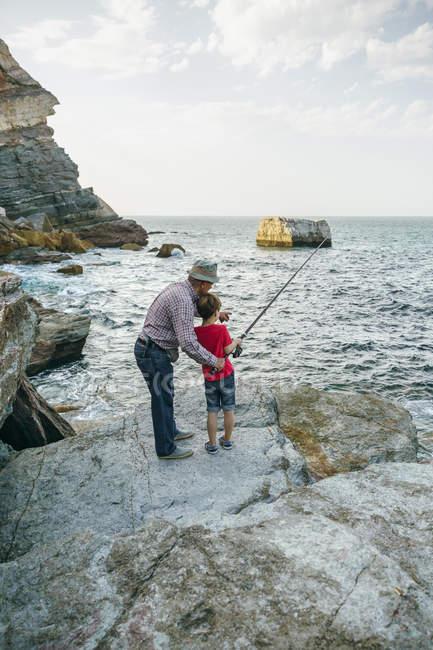 Abuelo y nieto juntos de pesca en el mar - foto de stock