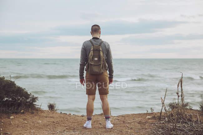 Jeune homme avec sac à dos debout et regardant la mer — Photo de stock