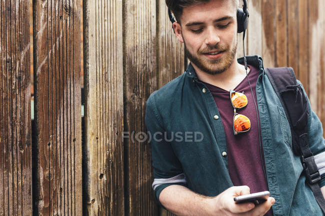 Young man listening music in headphones and using smart — Stock Photo