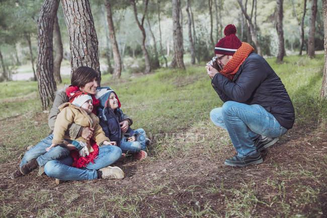 Pai tirando uma foto de sua família na floresta — Fotografia de Stock