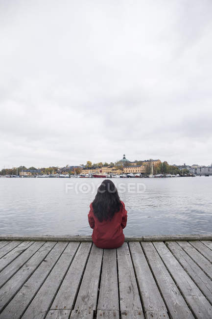 Back view of woman sitting on pier looking to the city — Stock Photo