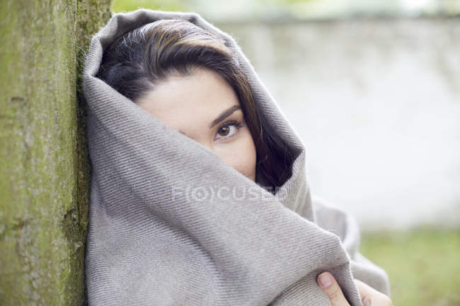 Woman wrapped in grey scarf leaning against tree trunk — Stock Photo