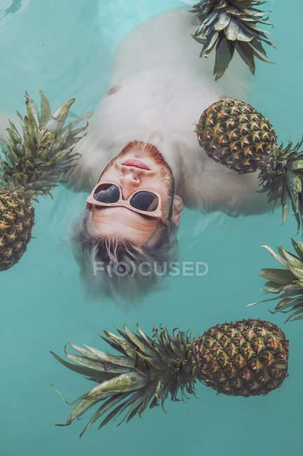 Jovem homem boiando na piscina rodeada por abacaxis — Fotografia de Stock