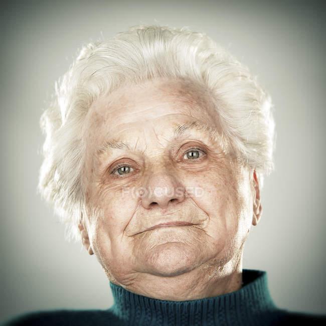 Retrato de mujer senior tranquila mirando a cámara - foto de stock