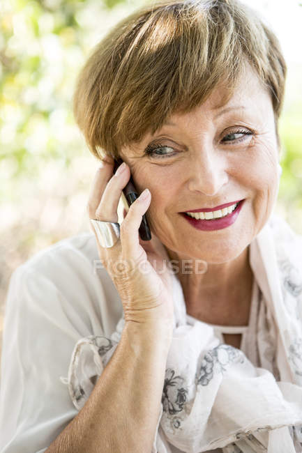 Portrait of senior woman on the phone outdoors — Stock Photo