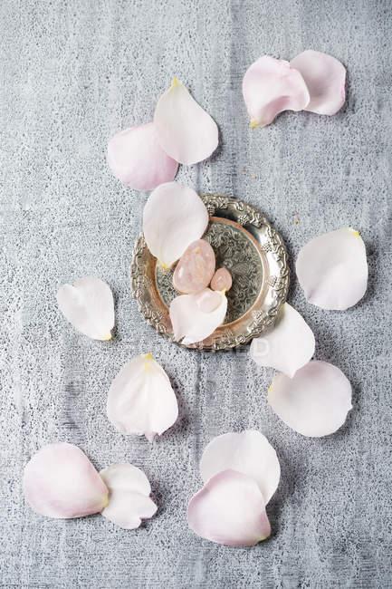 Rosenquarz mit Rosenblättern auf grauer Oberfläche — Stockfoto