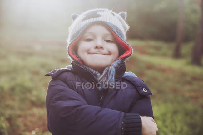 Портрет мальчика ухмыляясь, ношение шерстяной шапке в лесу — стоковое фото