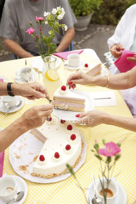 Руки положить крем торт на плиты — стоковое фото