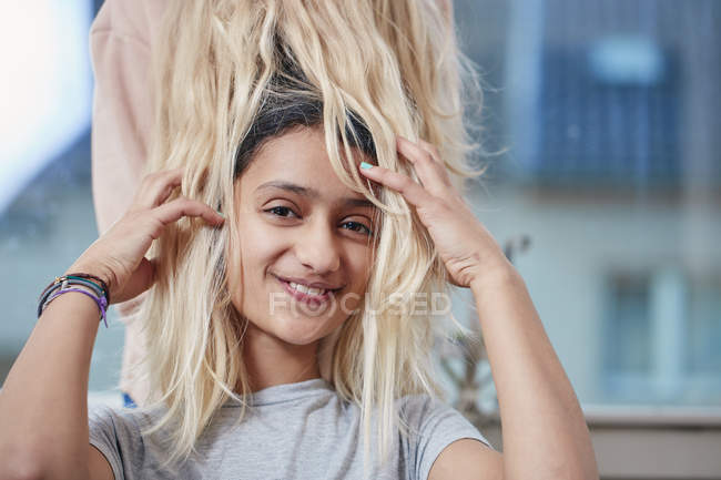 Portrait of smiling girl playing with hair of friend — Stock Photo