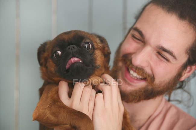 Сміючись чоловік тримає Пті Brabancon — стокове фото
