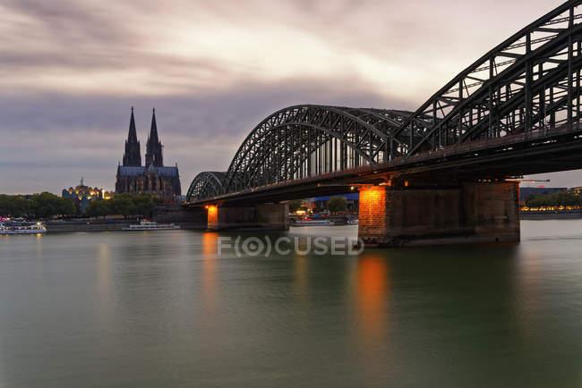 Deutschland, Köln, Blick auf den Kölner Dom mit Hohenzollernbrücke im Vordergrund in der Abenddämmerung — Stockfoto