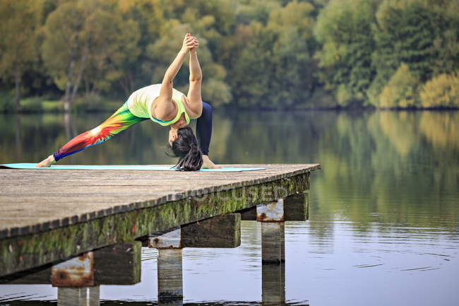 Young woman doing yoga exercise at a lake — Stock Photo