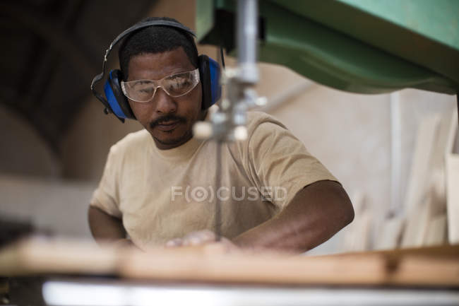 Craftsman in protective eyeglasses working in wood work — Stock Photo