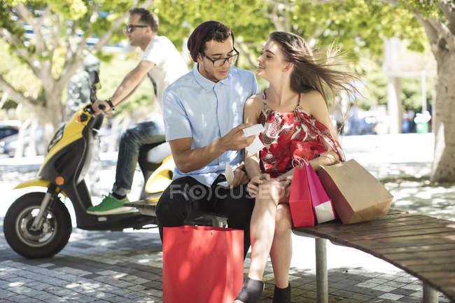 Хипстер, сидящий на скамейке, проверяет счет за покупки с девушкой, держащей сумки на городской площади, мужчина на скутере позади них — стоковое фото