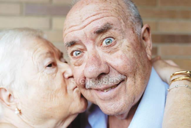Senior homme tirant grimace tandis que sa femme lui baiser — Photo de stock