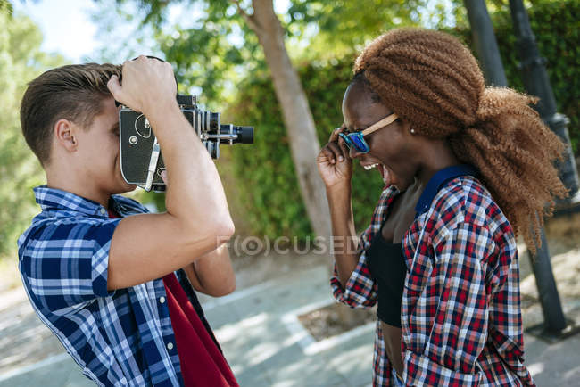 Young man filming girlfriend with old-fashioned camera — Stock Photo