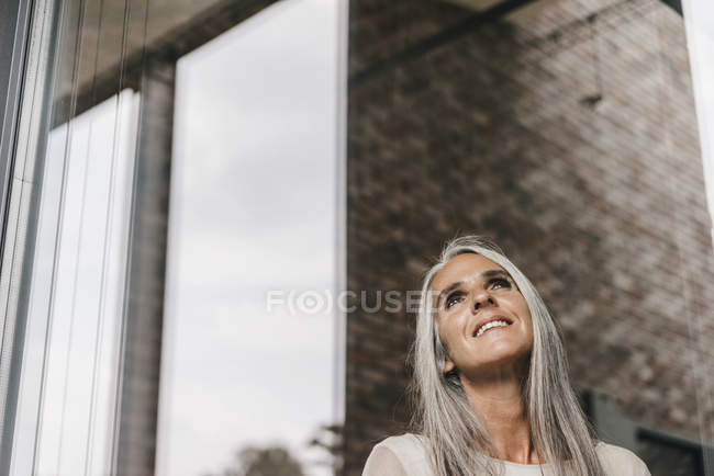 Smiling woman with long grey hair looking out of window — Stock Photo
