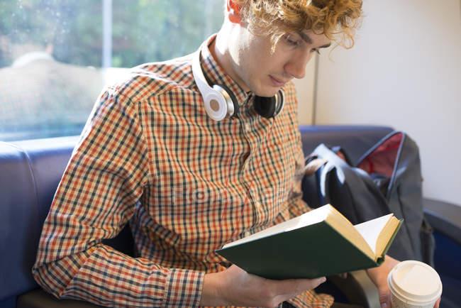 Молодой человек с кофе будет сидеть в поезде и читать книгу — стоковое фото