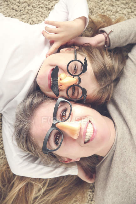 Portrait of mother and daughter lying on the carpet wearing funny glasses with plastic nose — Stock Photo