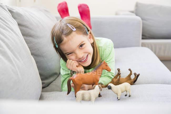 Портрет усміхнений дівчинка, лежачи на дивані з фігурки тварин — стокове фото