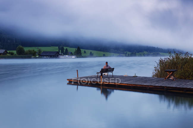 Austria, Carinthia, Man sitting on jetty at Lake Weissensee — Stock Photo