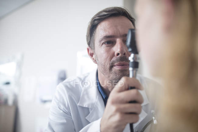 Doctor using an otoscope — Stock Photo