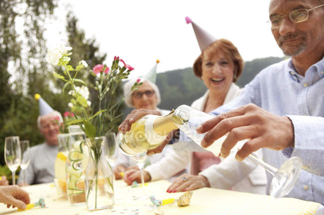 Senior people celebrating, man pouring champagne into glass — Stock Photo
