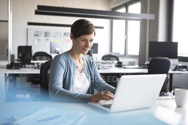 Усміхаючись бізнес-леді за допомогою ноутбука в офісі — стокове фото
