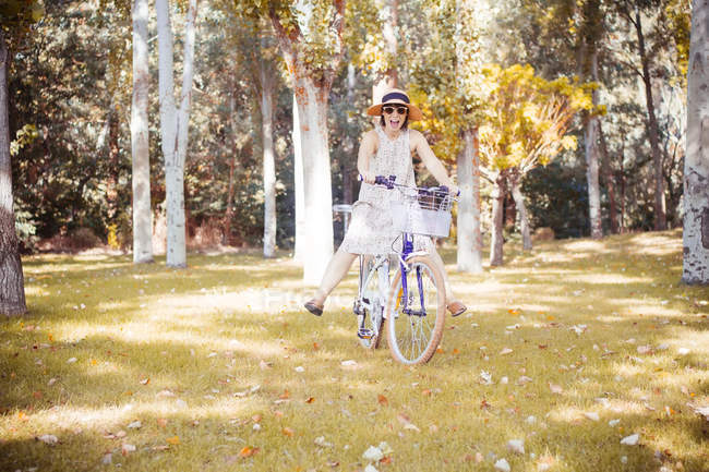 Woman balancing on bicycle in autumnal park — Stock Photo