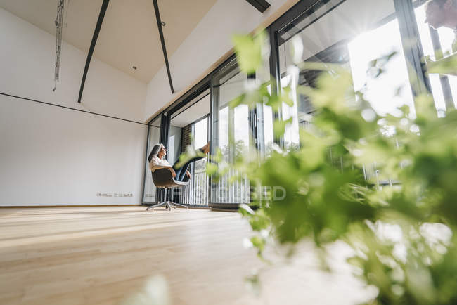 Woman sitting on chair at the window in empty room with plant — Stock Photo