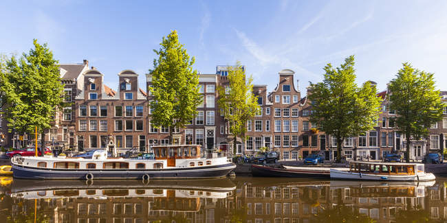 Netherlands, Amsterdam, Prinsengracht, typical houses and houseboat on canal — Stock Photo