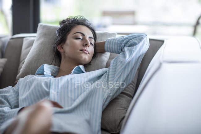 Jovem relaxante em um sofá — Fotografia de Stock