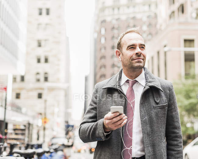 USA, New York City, businessman on the move in Manhattan with smartphone — Stock Photo