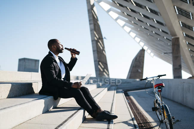 Businessman sitting on stairs and drinking beer — Stock Photo