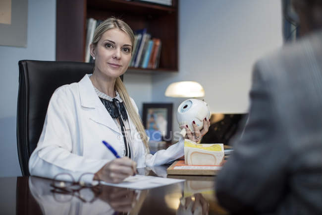 Female optometrist talking to patient, holding model of eyball — Stock Photo