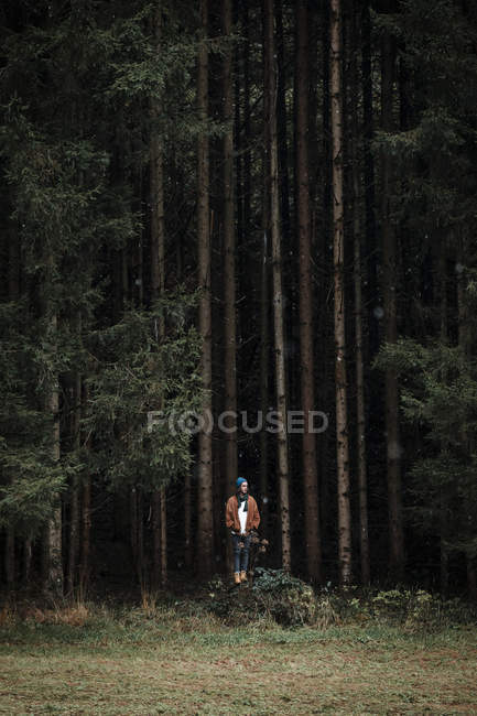 Young man standing in front of coniferous forest — Stock Photo