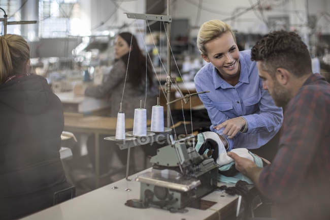 Staff working in textile factory at tables with sewing machines — Stock Photo