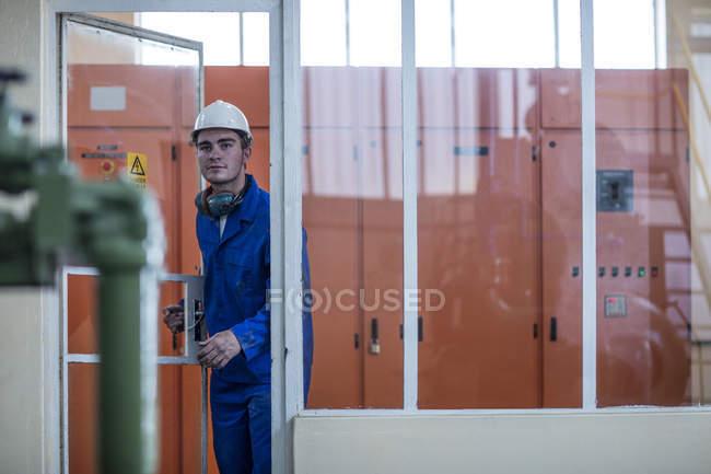 Arbeiter verlässt Technikraum in Fabrik — Stockfoto