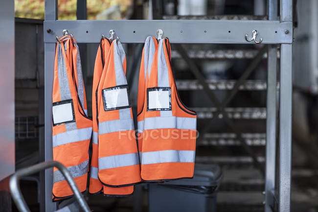 Three safety vests hanging on hooks in factory — Stock Photo