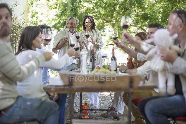 Couple de personnes âgées debout ensemble comme amis et famille soulève un toast avec verres à vin en dehors des repas jardin — Photo de stock