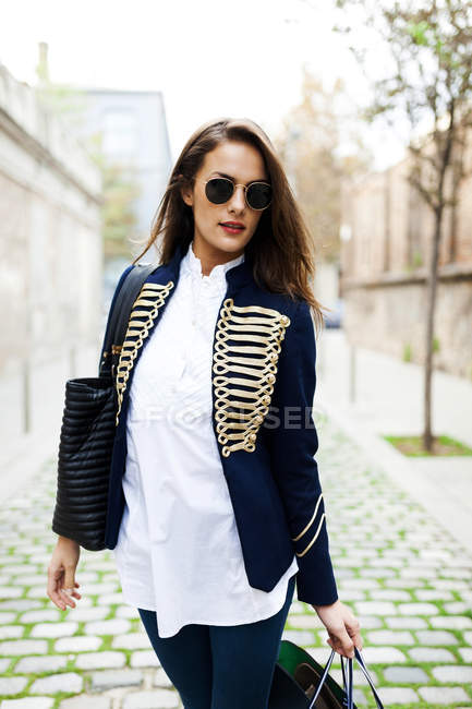 Fashionable young woman wearing sunglasses carrying shopping bags — Stock Photo