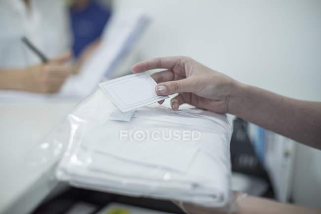 Frau mit weißen Kittel in Kunststoffverpackungen und Namensschild — Stockfoto