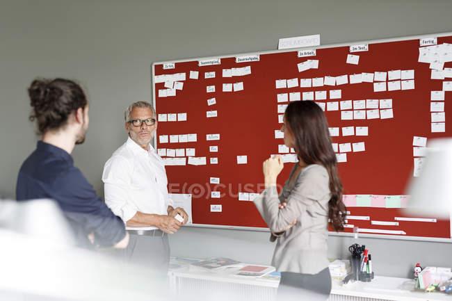 Chers collègues discutant à bord dans un bureau moderne — Photo de stock