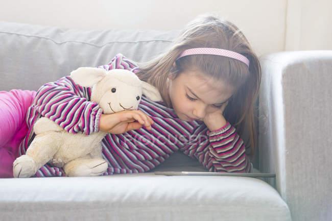 Petite fille couchée sur le canapé avec un jouet doux et utilisant une tablette — Photo de stock