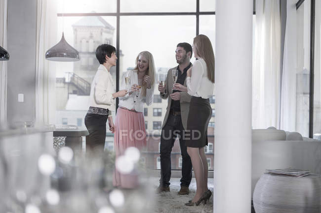 Friends holding champagne glasses socializing in a city apartment — Stock Photo