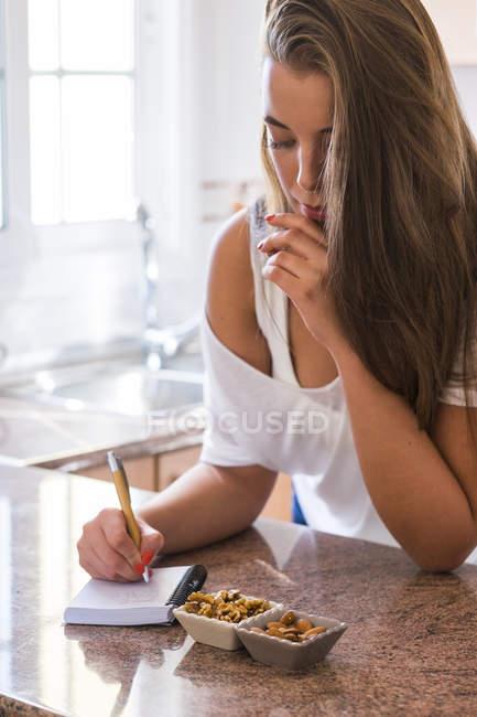 Mulher jovem, escrevendo no bloco de notas na cozinha mesa com petiscos — Fotografia de Stock