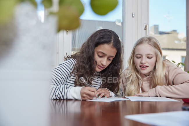 Two girls doing homework together at home — Stock Photo