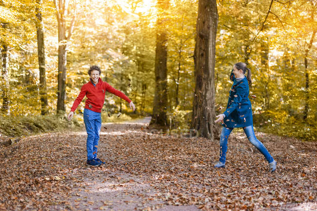 Mère et fils jetant avec des feuilles d'automne dans la forêt — Photo de stock