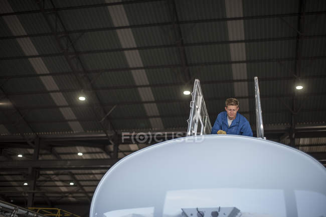 Trabalhador da fábrica em cima do recipiente do caminhão na fábrica — Fotografia de Stock