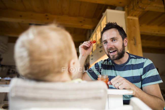 Батько годування маленьку дитину вдома — стокове фото